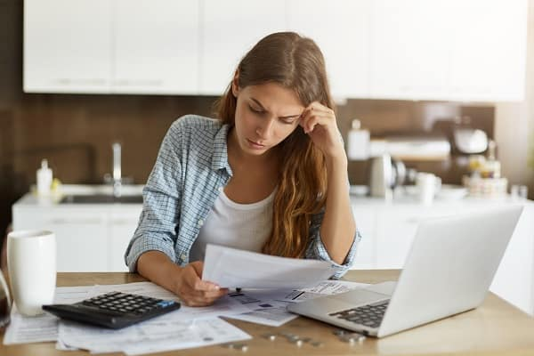A woman worries as she looks over household bills